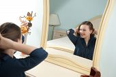 picture of cheval  - Young woman is making her hairstyle in front of mirror - JPG