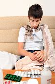 stock photo of home remedy  - Sick Teenager on the Sofa at the Home with Pills on foreground - JPG
