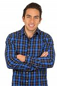 handsome young latin man wearing a blue plaid shirt posing