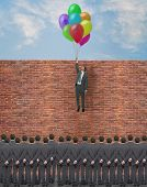 pic of overcoming obstacles  - young businessman overcomes an obstacle for the consideration of the crowd - JPG