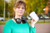 stock photo of girl walking away  - Happy young student woman drinking take away coffee and walking in an urban city park - JPG