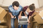 stock photo of  habits  - The young happy couple searching for apartments with laptop - JPG