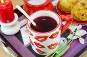 stock photo of mug shot  - Lip patterned tea mug and corn bread on a tray shot closeup - JPG