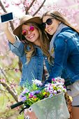 stock photo of two women taking cell phone  - Portrait of two beautiful young women taking a selfie in the field.