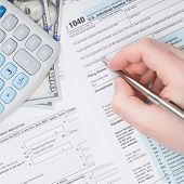 stock photo of cpa  - Taxpayer filling out U - JPG