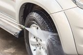 stock photo of water jet  - Close up Car washing with high pressure water jet - JPG