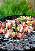 stock photo of bbq food  - Summer barbecue. Meat BBQ with herbs and vegetables. Outdoor grill food ** Note: Shallow depth of field - JPG