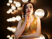 stock photo of superstars  - Superstar woman wearing golden shining dress posing - JPG