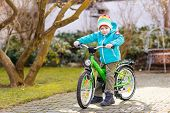 foto of preschool  - Little preschool kid boy riding with his first green bike in the city - JPG