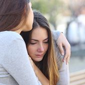 stock photo of comfort  - Sad girl crying and a friend comforting her outdoors in a park - JPG