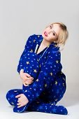 image of nighties  - Smiling beautiful girl siting in funny blue colored pajamas with star pattern and a hood - JPG