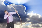 stock photo of archery  - Businessman practicing archery with clouds in background - JPG