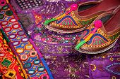 stock photo of flea  - Colorful ethnic shoes cushion cover and Rajasthan belts on flea market in India - JPG