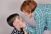stock photo of scared  - Woman scolding and holding the head of the scared young boy - JPG