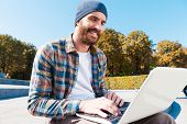 picture of long beard  - Long angle view of handsome young bearded man smiling while working on laptop - JPG