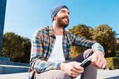 stock photo of long beard  - Long angle view of handsome young bearded man smiling while listening to music - JPG