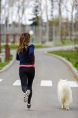 stock photo of dog park  - attractive sport girl running with dog in park - JPG