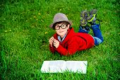 stock photo of 7-year-old  - Cute 7 years old boy lying on a grass and reading a book - JPG