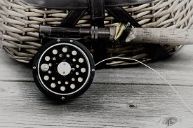 picture of fly rod  - Vintage concept with grain of an antique fly fishing reel rod and artificial flies in front of creel with rustic wood underneath - JPG