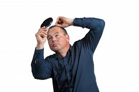 foto of bald headed  - Worried guy having a closer look at his balding head - JPG