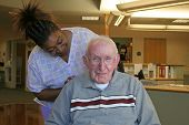 stock photo of male nurses  - the loving touch of nursing staff has a great effect on a nursing home resident - JPG