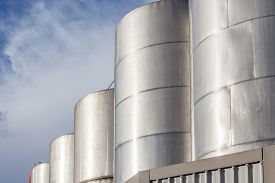 foto of petrol  - Large metal industrial tanks for petrol and oil of refinery industry with beautiful clear blue sky - JPG