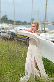 foto of wind-rose  - Attractive sensual young bride in long beige wedding dress with posy of alstromeria and rose flowers coral color holding fabric on wind standing on green grass in yahct club berth horizontal picture - JPG