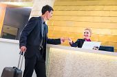 Hotel receptionist check in man giving key card poster