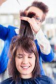 Female coiffeur cutting women hair in hairdresser shop poster