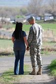 stock photo of soldiers  - Young couple on a country dirt lane holding hands and saying goodbye - JPG