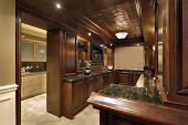 Bar in basement of luxury home with view into pantry