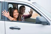 Happy multiracial couple on car travel together on summer vacation. Joyful young people smiling wavi poster