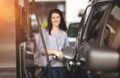 Pretty woman filling her car with petrol at gas station poster