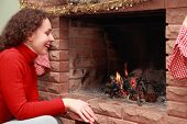 beautiful young woman in red sweater sits near fireplace and smiles