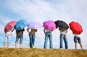O grupo de pessoas com as guarda-chuvas