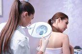 Woman visiting dermatologist at clinic poster