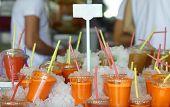 Plastic glasses with cold freshly squeezed carrot juice