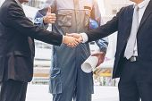 Постер, плакат: Businessmen Handshake With Engineer Thumbs Up