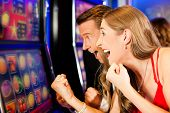 stock photo of arcade  - Couple in Casino on a slot machine - JPG