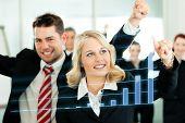 Negócios - apresentação dentro de uma equipe; uma colega mostra o gráfico na tela