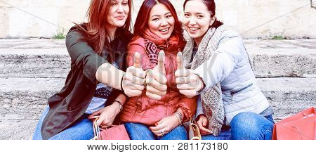 poster of Happy Multiracial Young Women Thumbs Up Sitting Outdoors At Day Time - Three Best Female Friends In