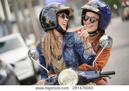 Happy young women riding scooter