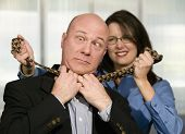image of strangle  - Businesswoman strangles a male coworker with his necktie - JPG