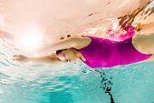 Focused Woman Swimming In Googles Underwater In Swimming Pool poster