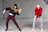 Couple Of Dancers In Action. Modern Style Boy And Girl Dancing Hip-hop On Studio Background. Skillfu poster
