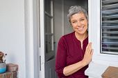 Portrait of senior woman standing while leaning against door at home and looking at camera. Smiling  poster