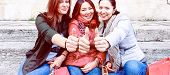 Happy Multiracial Young Women Thumbs Up Sitting Outdoors At Day Time - Three Best Female Friends In  poster