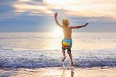 Child Playing On Ocean Beach. Kid Jumping In The Waves At Sunset. Sea Vacation For Family With Kids. poster