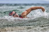 Triathlon swim tired swimmer swimming in ocean in wave and rain storm . Professional male triathlon  poster