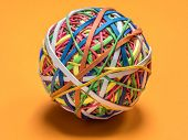 Colorful rubber band ball on orange background poster